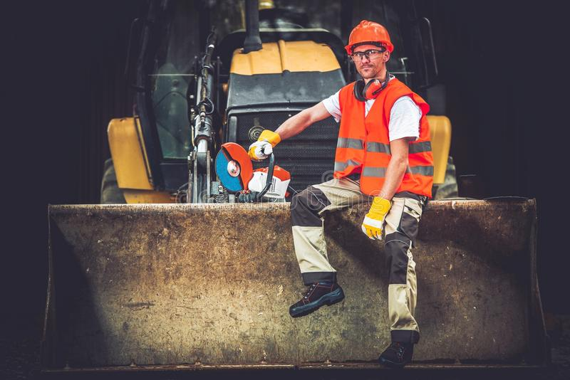 Happy Construction Worker. Bulldozer Works Concept. Young Caucasian Men Seating and Relaxing on Bulldozer Blade. Happy Construction Worker. Ground Works stock photos