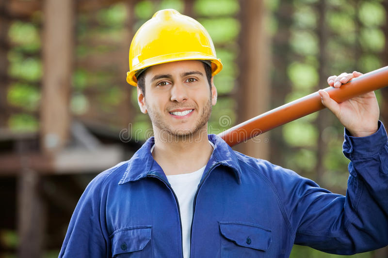 Happy Construction Worker Holding Pipe. Portrait of happy construction worker holding pipe at site stock image