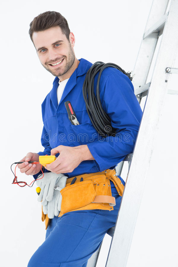 Happy construction worker leaning on ladder royalty free stock photography