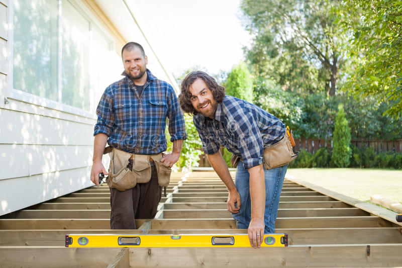 Happy Construction Workers With Spirit Level At. Portrait of happy construction worker checking level of wood with spirit level while standing with coworker at stock photography