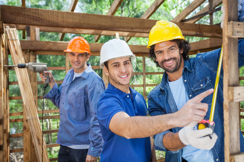 Happy Construction Workers Working In Wooden Cabin royalty free stock images