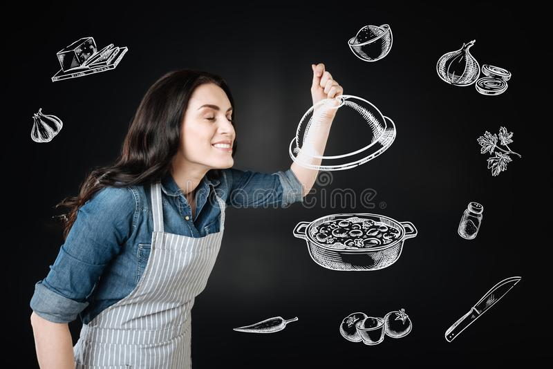Happy cook closing her eyes while smelling the dish. Tasty smell. Professional experienced cook being in the kitchen and standing with her eyes closed while stock photos