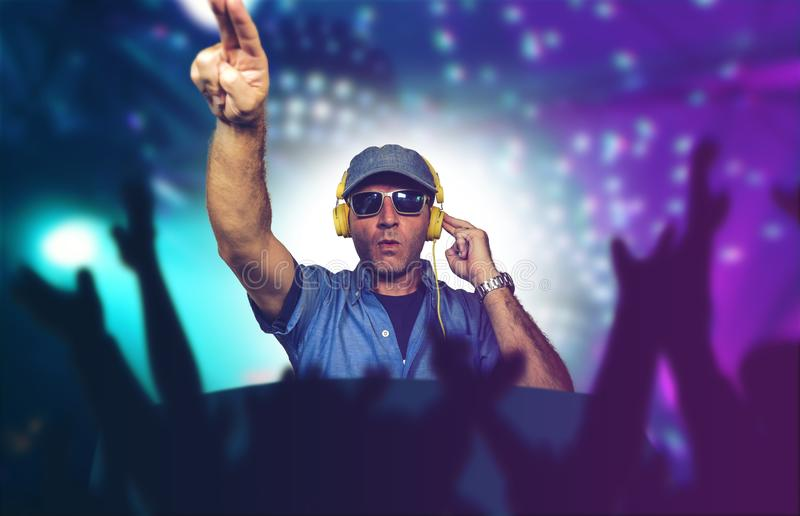 Happy and cool DJ playing music at party event in night club mixing techno songs on laser and flash lights background cheered with. Young happy and cool DJ royalty free stock photos