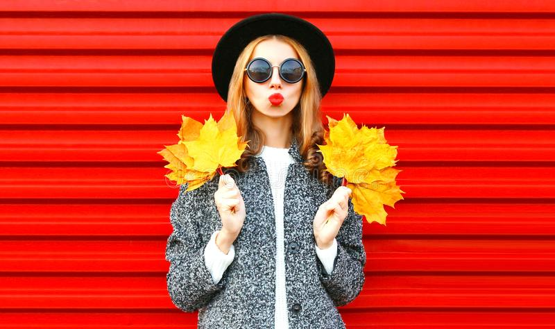 Happy cool girl with red lips holds yellow maple leaves. On background stock photography