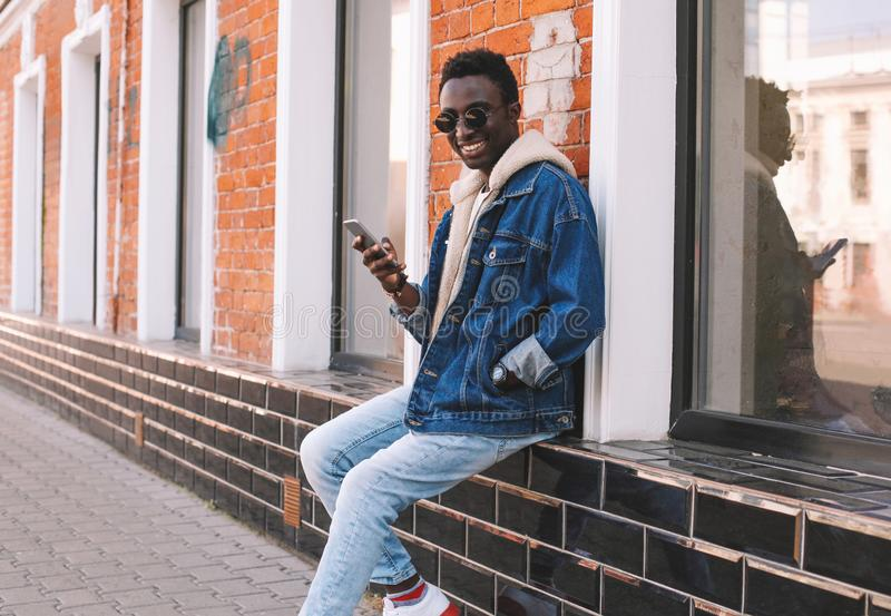 Happy cool smiling african man with smartphone sitting on city street over brick wall. Background stock photography
