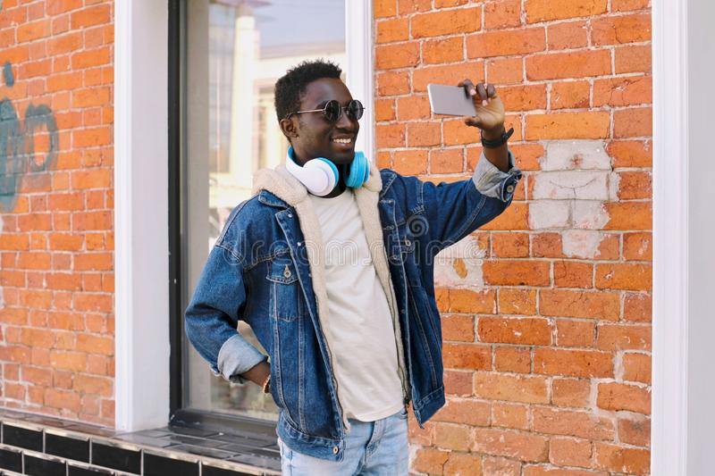 Happy cool smiling african man taking selfie picture by smartphone on city street over brick wall royalty free stock image