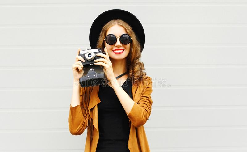 Happy cool young woman model with retro film camera wearing a elegant hat, brown jacket royalty free stock photos