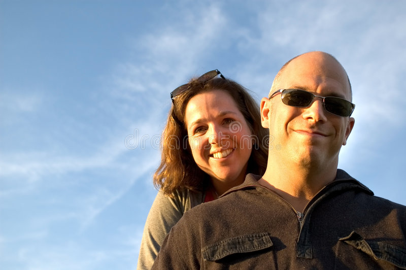 Happy couple. Happy woman and man (facing light at sunset - Models are 35 years old