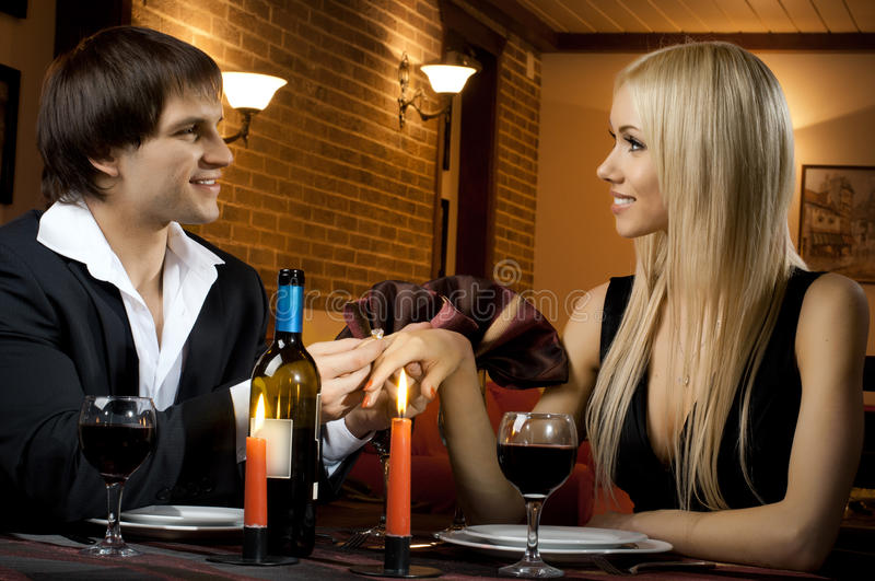 Happy couple. Romentic evening date in hotel room, or supper in restaurant, guy make engagement ring his beautiful women royalty free stock photo