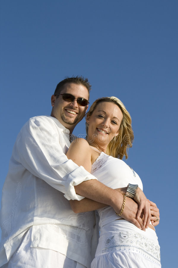 Happy Couple. Man and a woman looking into the camera. Both wearing white clothes stock images