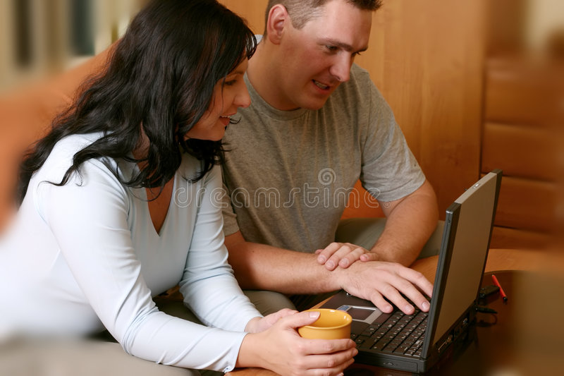 Happy Couple. Smiling couple sitting on the sofa with laptop on the table
