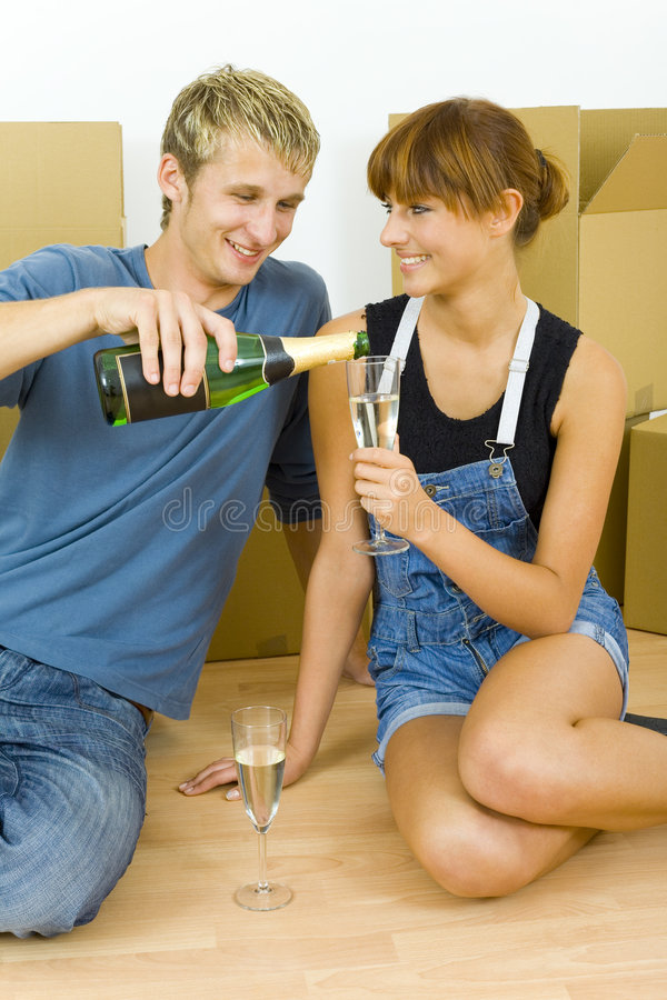 Happy couple. Young couple sitting on the floor in flat. They're looking happy. Celebrating removal with champagne royalty free stock photos