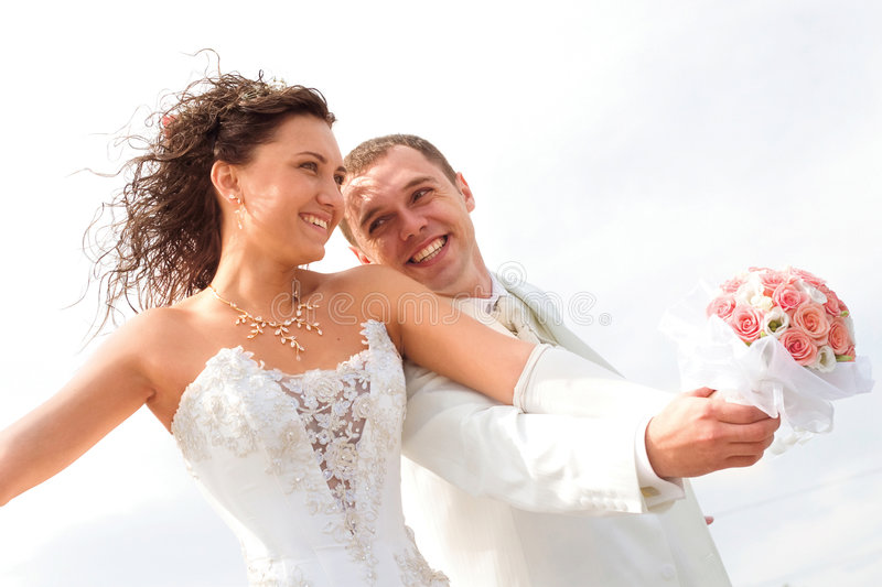 Happy couple. Young couple in wedding wear with bouquet of roses