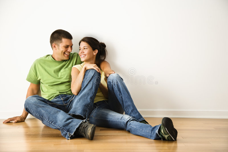Happy couple. Attractive young adult couple sitting close on hardwood floor in home smiling stock photos