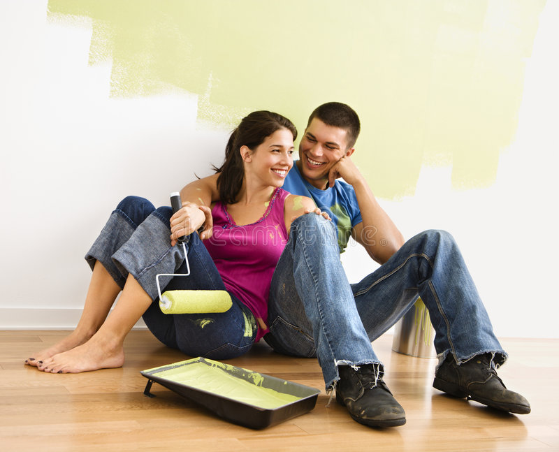 Happy couple. Couple sitting on floor smiling in front of partially painted wall in home