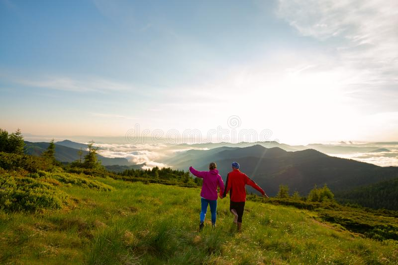 Happy couple of adventurers is running and having fun. Delighted, from the awesome view of the mountains during sunset. Epic travel in the mountains. Wide royalty free stock photos