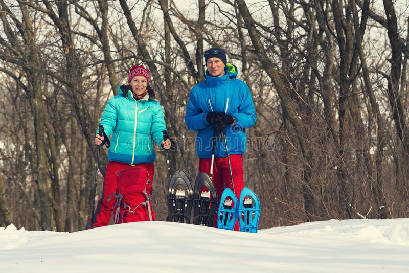 Happy couple of adventurers stands in a winter forest. Next to snowshoes and other equipment for travel in wilderness among deep snow stock photo