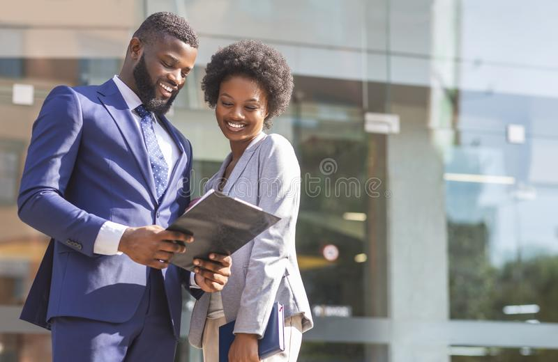 Couple of african american business partners working while standing outdoors royalty free stock images