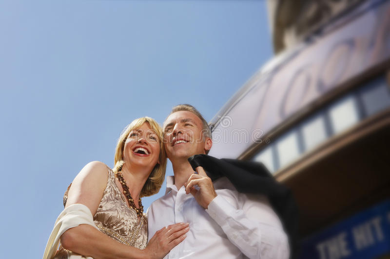 Happy Couple Against Building And Sky. Low angle view of a well dressed smiling couple standing against building and sky stock photo