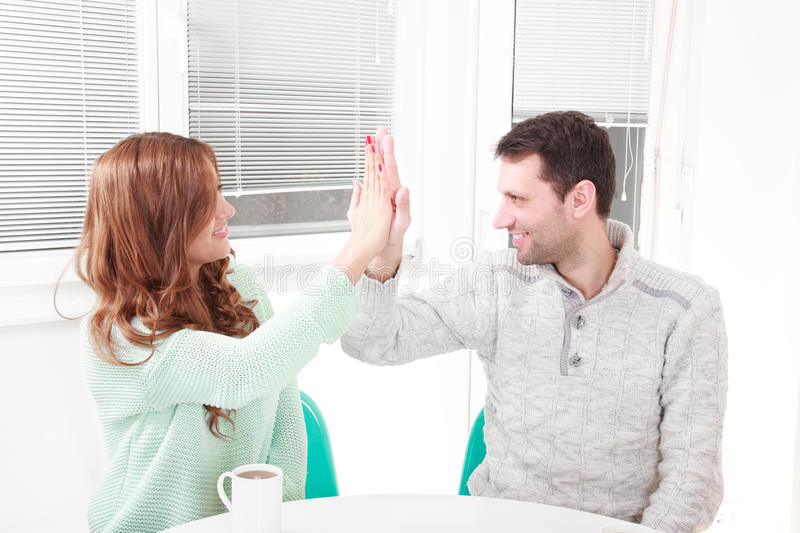 Happy couple agrees with the agreement. Having agreement with gesture give me five, symbol hand on hand. Causal couple clapping hands in their living room royalty free stock photos