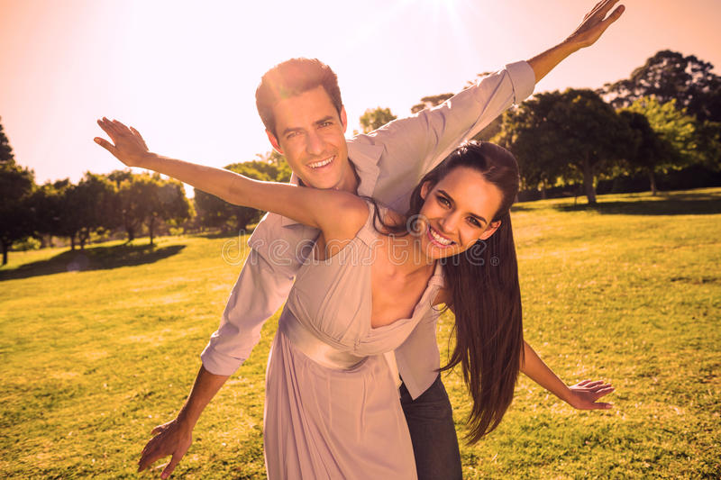 Happy couple with arms outstretched at park stock images