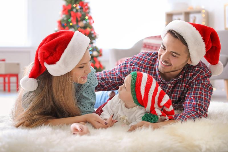 Happy couple with baby in Christmas hats. At home royalty free stock photography