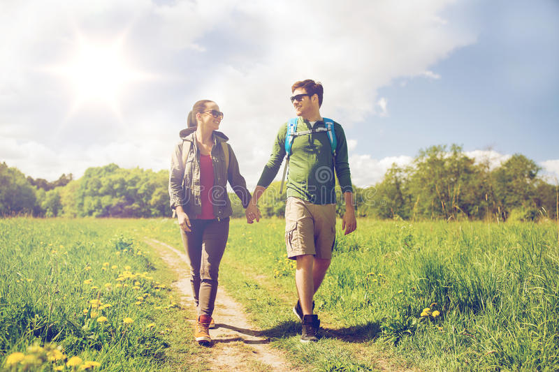 Happy couple with backpacks hiking outdoors stock image