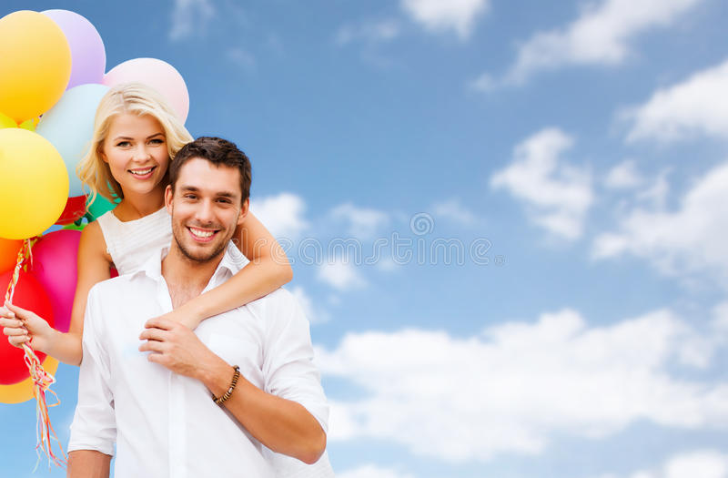 Happy couple with balloons over blue sky stock image