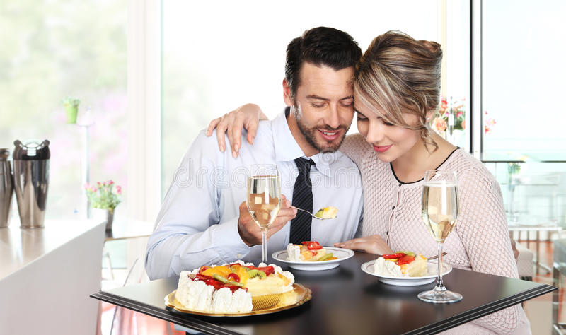 Happy couple at the bar with wine and fruit cake royalty free stock image