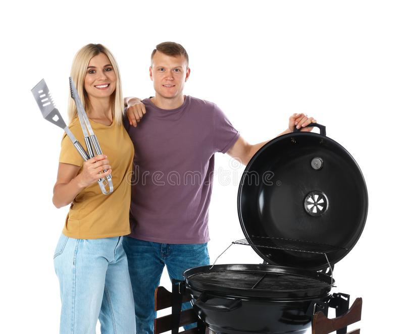 Happy couple with barbecue  and utensils on white background. Happy couple with barbecue grill and utensils on white background stock photo