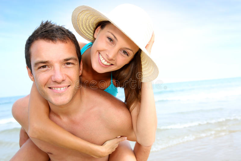 Happy couple at the beach. Man giving piggyback ride to girlfriend by the ocean royalty free stock image