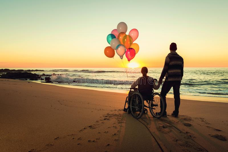 Happiness is everywhwere. Happy couple at the beach, where women is on a wheelchair holding balloons on her hands stock image