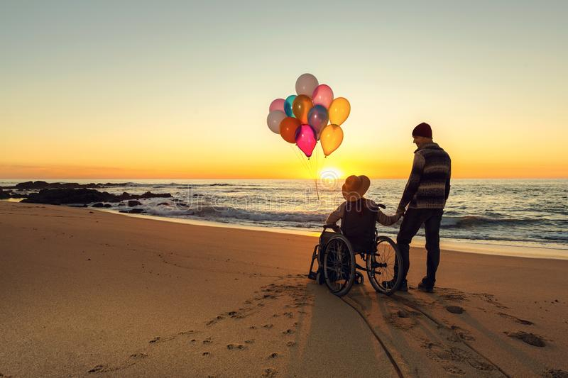 Happiness is everywhwere. Happy couple at the beach, where women is on a wheelchair holding balloons on her hands royalty free stock image