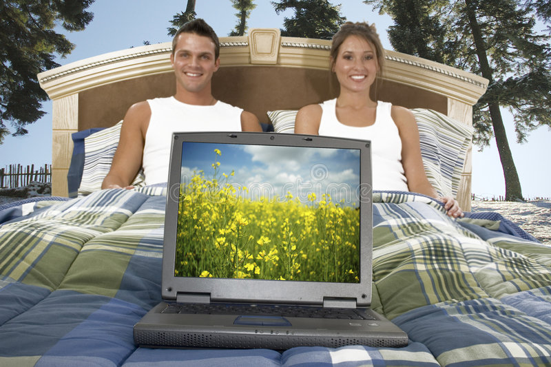 Happy couple in bed stock image