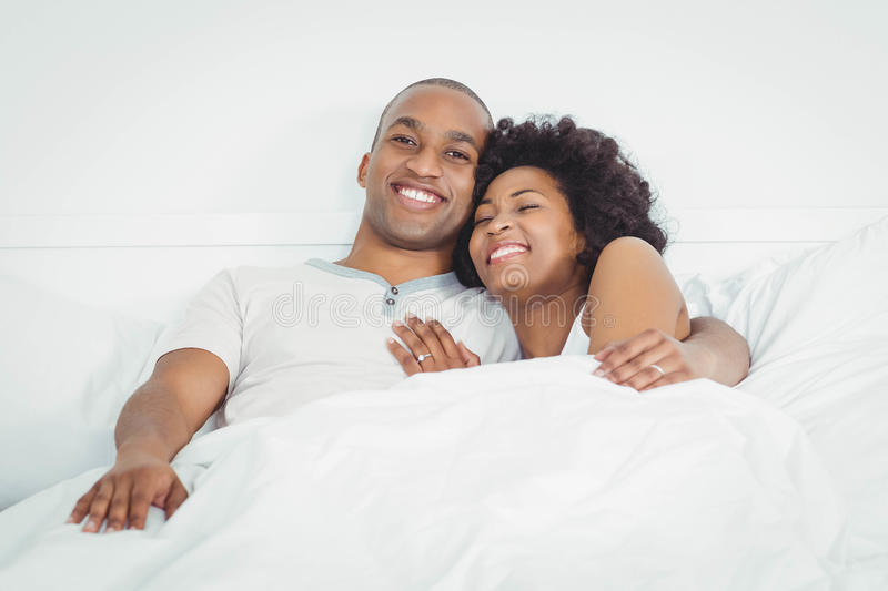 Happy couple on bed stock photos