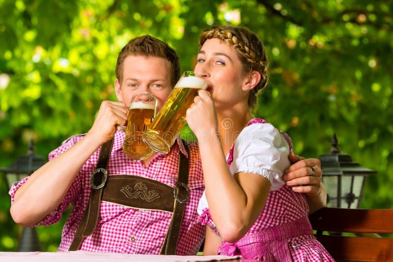 Happy Couple in Beer garden drinking beer royalty free stock images