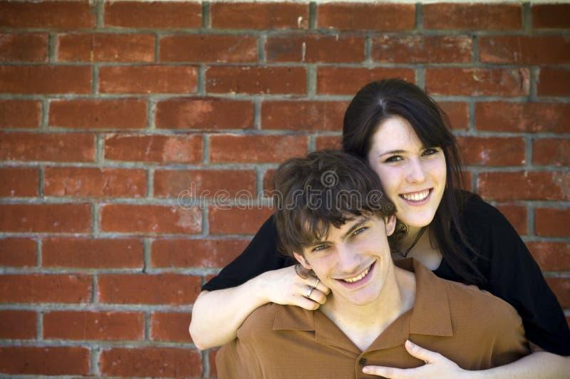 Happy Couple And Brick Wall Stock Photo
