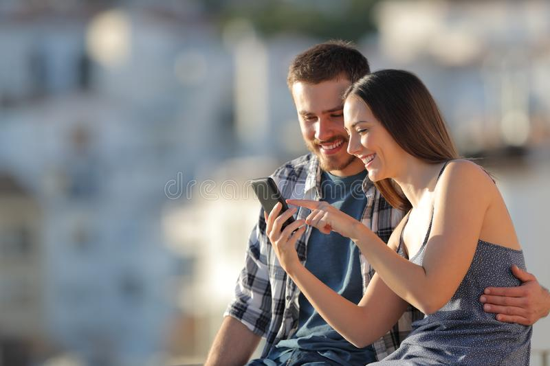 Happy couple browsing phone content in a town outskirts royalty free stock image