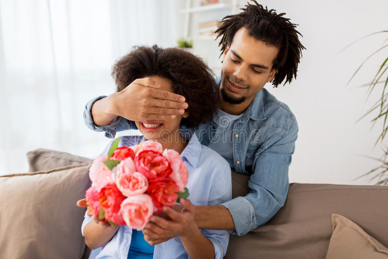 Happy couple with bunch of flowers at home stock image