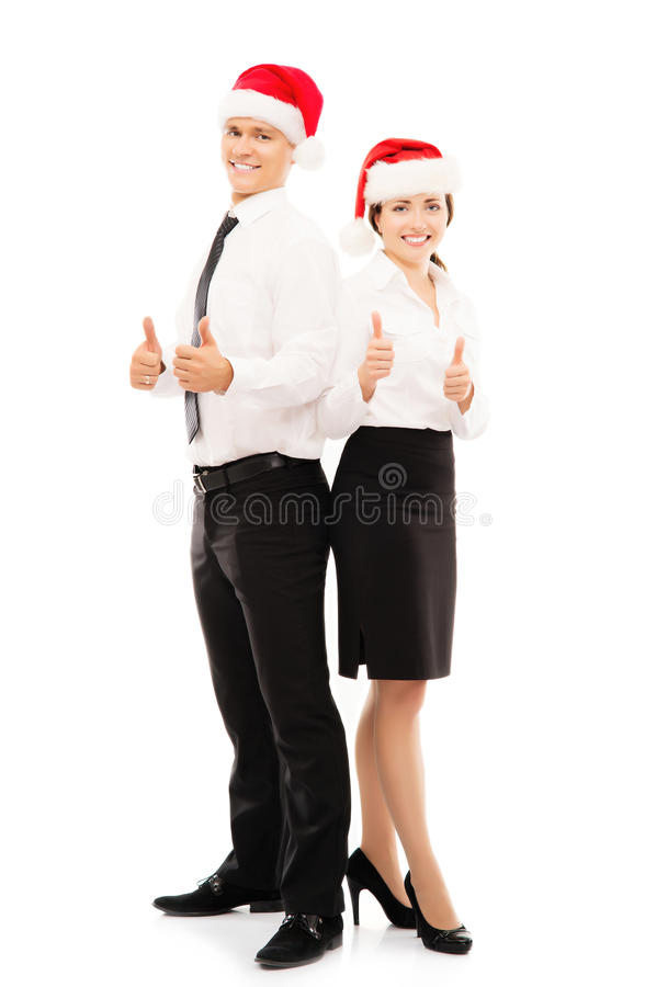 Happy couple of business persons in Christmas hats. Happy couple of young business persons posing in Christmas hats and holding thumbs up. Image isolated on royalty free stock images