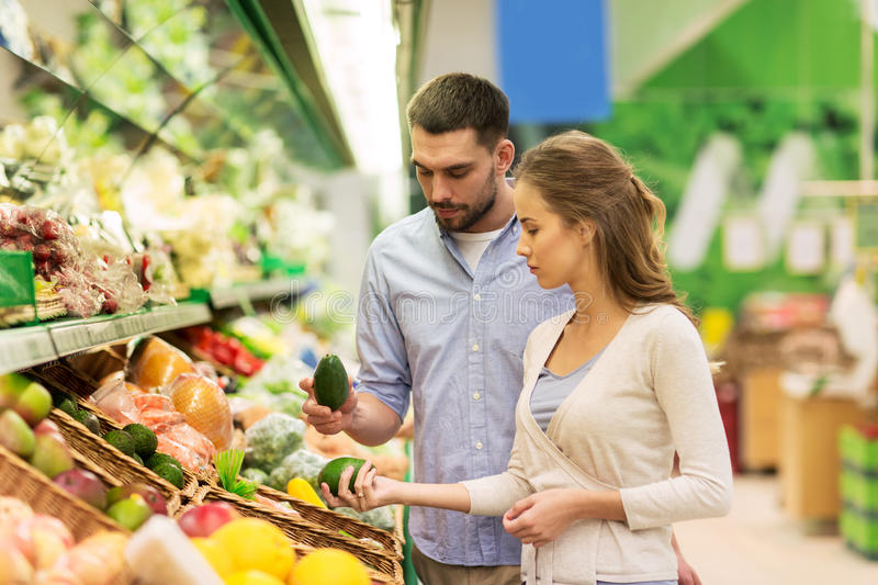 Happy couple buying avocado at grocery store stock photography