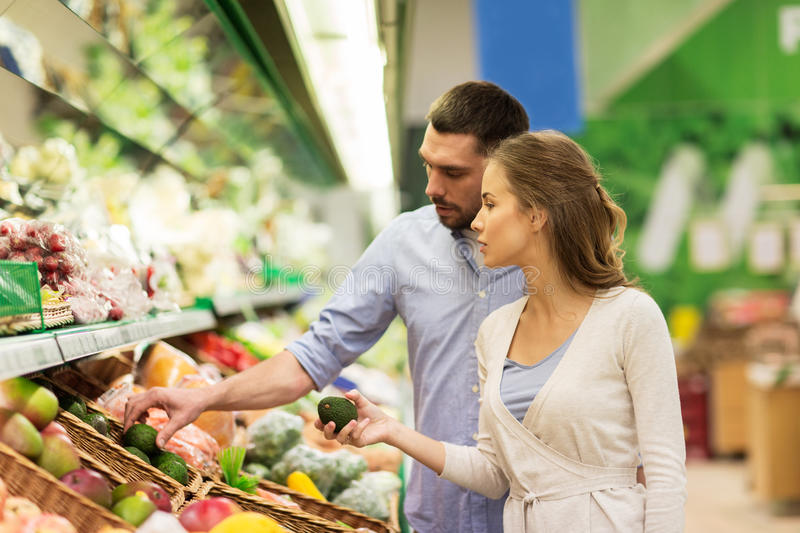Happy couple buying avocado at grocery store. Shopping, food, sale, consumerism and people concept - happy couple buying avocado at grocery store or supermarket stock photo