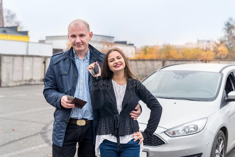 Happy couple buying new car posing outdoors royalty free stock image