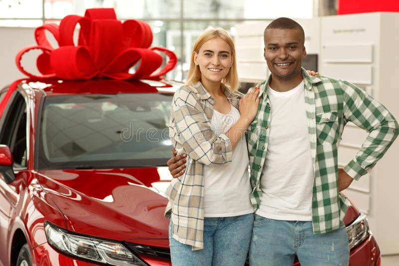 Happy couple buying new car together at the dealership. Horizontal shot of a happy young interracial couple embracing smiling to the camera standing in front of royalty free stock photos