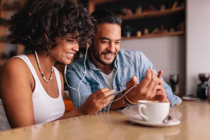 Happy couple at cafe having video chat on mobile phone stock photo