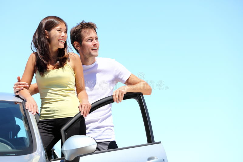 Happy Couple with car. Young interracial couple standing with car looking at the sky with copy space