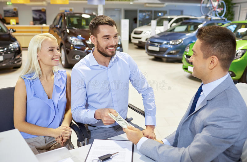 Happy couple with car dealer in auto show or salon stock photo