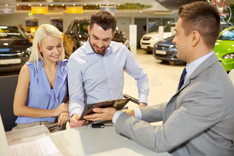 Happy couple with car dealer in auto show or salon. Auto business, sale and people concept - happy couple with dealer buying car in auto show or salon stock images