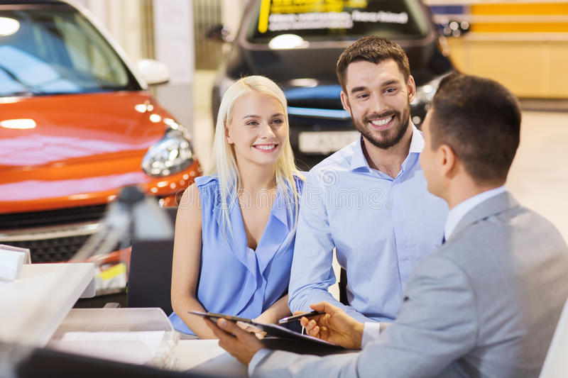 Happy couple with car dealer in auto show or salon. Auto business, sale and people concept - happy couple with dealer buying car in auto show or salon stock image
