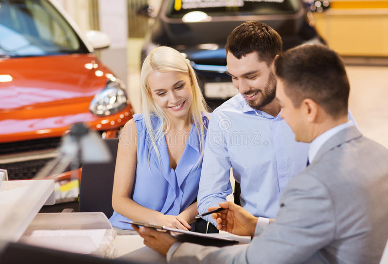 Happy couple with car dealer in auto show or salon. Auto business, sale and people concept - happy couple with dealer buying car in auto show or salon stock photography